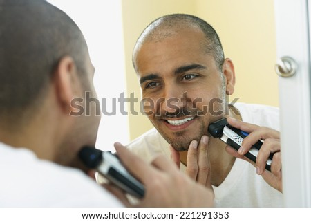 Middle Eastern man shaving with electric razor - stock photo