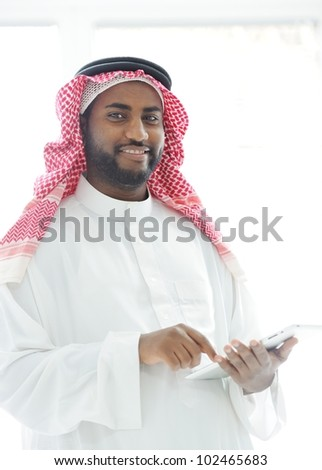 Middle eastern man with gulf clothes using tablet at office - stock photo