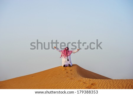 Middle eastern way dressed Arabic man poses in the desert sunset time. - stock photo