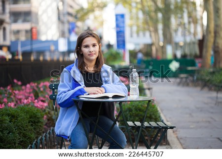 Middle School girl sitting in a city park in new york reading a book with a bottle of water - stock photo
