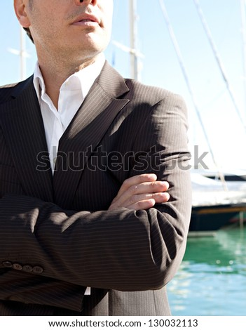 Middle section of a smart businessman wearing a suit and standing by a luxury yachts marine with his arms crossed against a blue sky. - stock photo