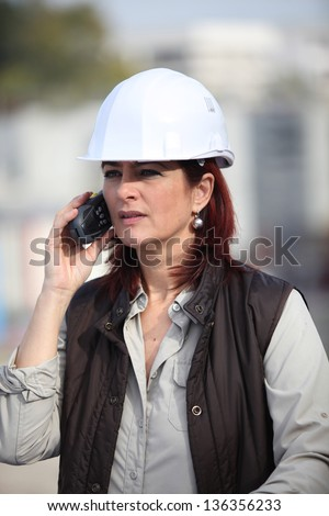 middleaged female architect making a call in construction site - stock photo