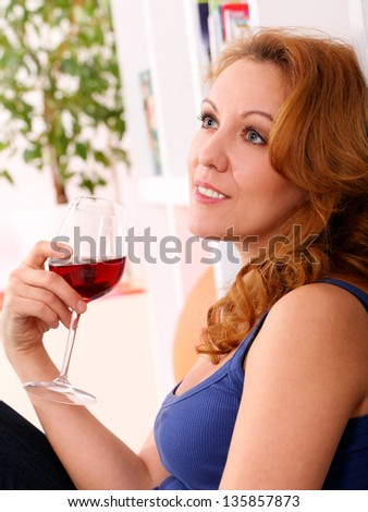 Middleaged happy woman enjoy glass of red wine at home - stock photo