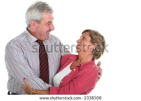 Middleaged man wearing tie embracing woman in her fifties - stock photo