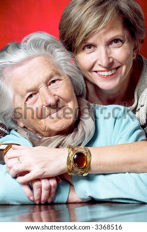 Middleaged woman hugs her mother and they both smile at the camera - stock photo