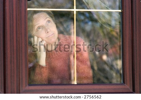 Middleaged woman looking through the window. - stock photo