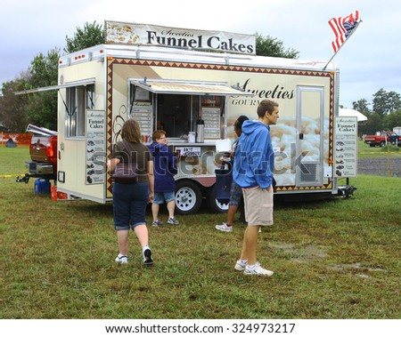 Middlesex, VIRGINIA - SEPTEMBER 26, 2015: Patrons at the Funnel cake concession trailer at the Wings Wheels & Keels 19th annual event held each September in Middlesex VA - stock photo
