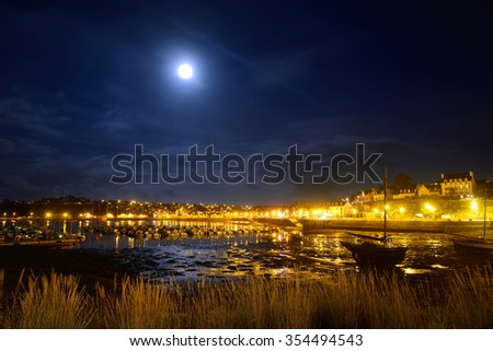 Midnight view of the port of Camaret sur mer, France, with rows of yachts on anchorage, orange lanterns and full moon - stock photo