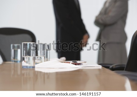 Midsection of a business couple standing with focus on conference table - stock photo