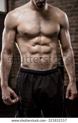 Midsection of a muscular man showing his body at the gym - stock photo