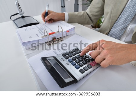 Midsection of accountant calculating bills at desk in office - stock photo
