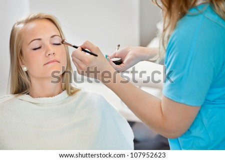 Midsection of beautician applying eye shadow to young woman at parlor - stock photo