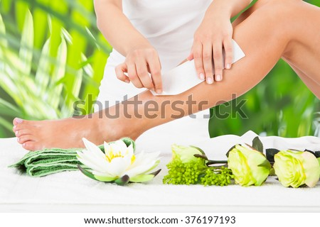 Midsection of beautician waxing woman's leg with wax strip at beauty spa - stock photo