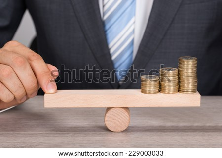 Midsection of businessman balancing coins on wooden seesaw at table - stock photo