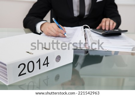 Midsection of businessman calculating taxes for 2014 at desk in office - stock photo