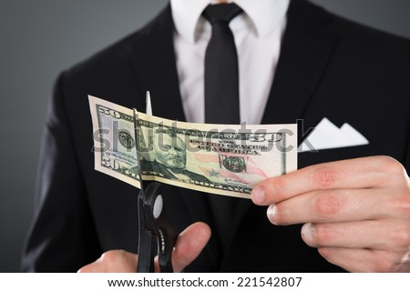 Midsection of businessman cutting dollar bill with scissors over gray background - stock photo