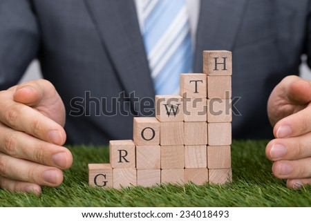Midsection of businessman protecting growth blocks on grass - stock photo