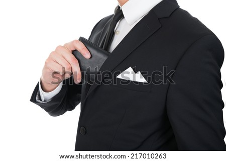 Midsection of businessman putting wallet in his pocket against white background - stock photo
