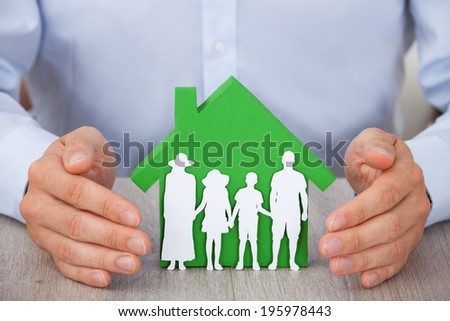 Midsection of businessman's hands protecting green model house and family at desk - stock photo