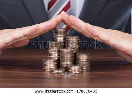 Midsection of businessman sheltering coin stacks on table - stock photo