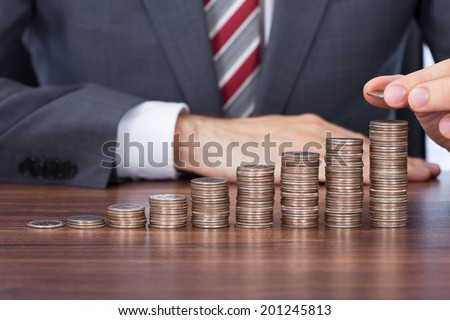 Midsection of businessman stacking coins in increasing order at desk - stock photo