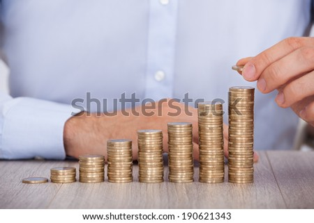 Midsection of businessman stacking euro coins at office desk - stock photo