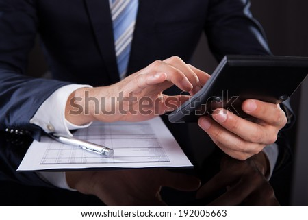 Midsection of businessman using calculator while checking financial expenses at desk - stock photo