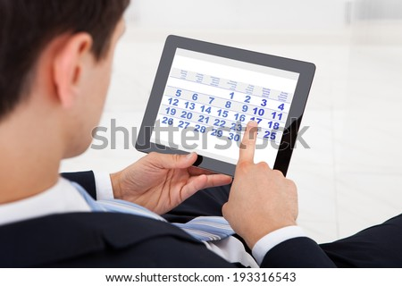 Midsection of businessman using calendar on digital tablet in office - stock photo