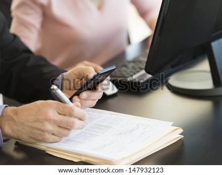 Midsection of businessman using smart phone while writing on document with colleague at desk in office - stock photo