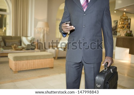 Midsection of businessman with cell phone and briefcase in hotel lobby - stock photo
