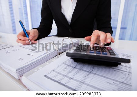 Midsection of businesswoman calculating tax at office desk - stock photo
