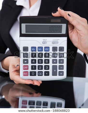 Midsection of businesswoman holding calculator at desk in office - stock photo