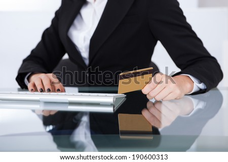 Midsection of businesswoman holding credit card at desk in office - stock photo