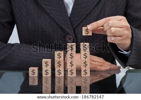 Midsection of businesswoman stacking dollar blocks at desk - stock photo