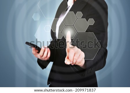 Midsection of businesswoman with mobile phone pressing button on touchscreen interface - stock photo