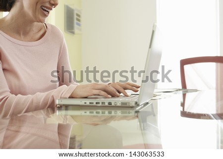 Midsection of cheerful businesswoman using laptop at office table - stock photo