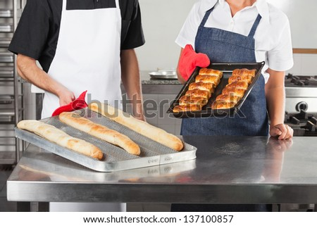 Midsection of chefs holding trays of baked breads in commercial kitchen - stock photo