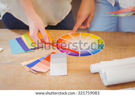 Midsection of colleagues pointing on multi colored flow charts on desk in office - stock photo