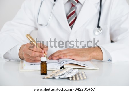 Midsection of doctor writing prescription at table against white background - stock photo
