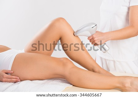 Midsection of female beautician using laser machine on customer's leg at salon - stock photo