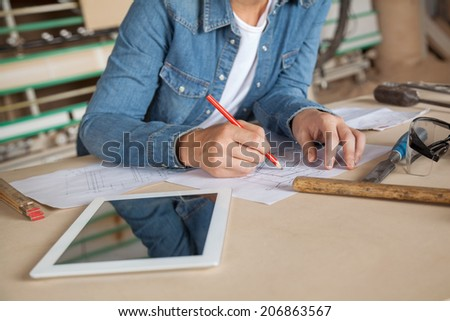 Midsection of female carpenter drawing on blueprint at table in workshop - stock photo
