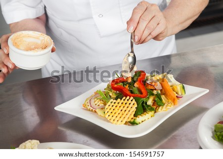 Midsection of female chef garnishing dish at kitchen counter - stock photo