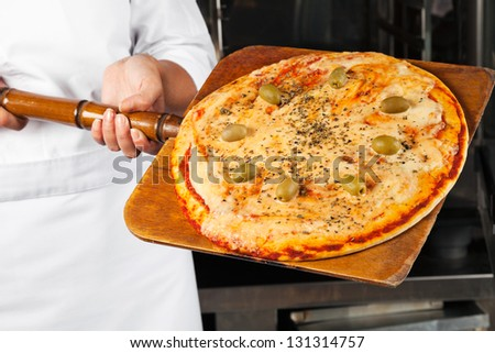 Midsection of female chef holding pizza on shovel - stock photo
