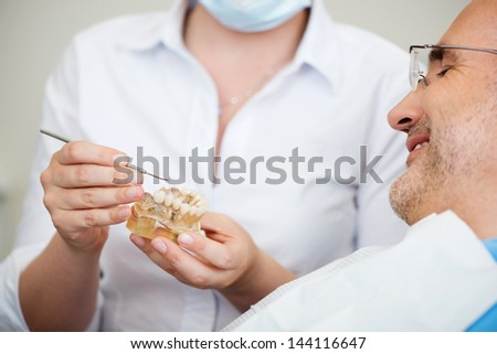 Midsection of female dentist explaining artificial teeth to patient in clinic - stock photo