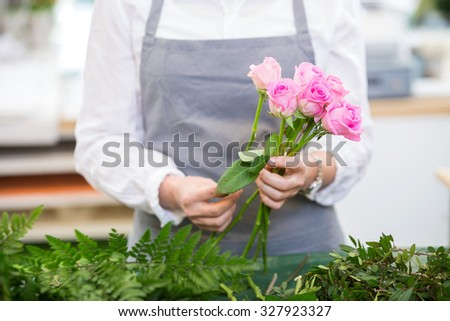 Midsection of florist making bouquet of roses in flower shop - stock photo