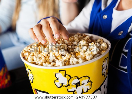Midsection of girl eating popcorn in cinema theater - stock photo