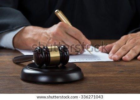Midsection of judge writing on paper at table in courtroom - stock photo