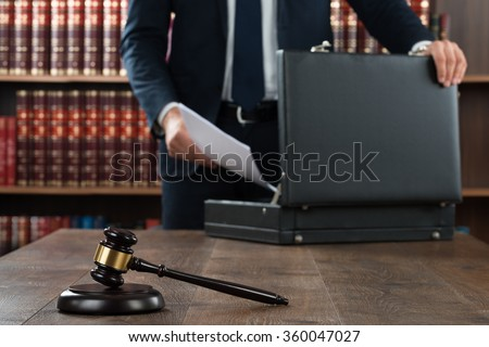 Midsection of lawyer putting documents in briefcase with gavel at desk in courtroom - stock photo