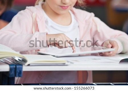 Midsection of little schoolgirl using digital tablet at desk in classroom - stock photo