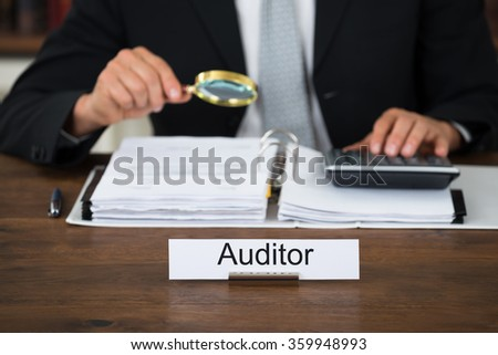 Midsection of male auditor scrutinizing financial documents at table in office - stock photo